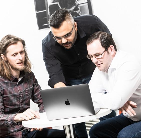 Jag, Simon & Ryan discuss around a laptop
