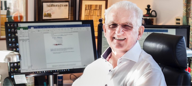 Chris Makin smiling at his desk
